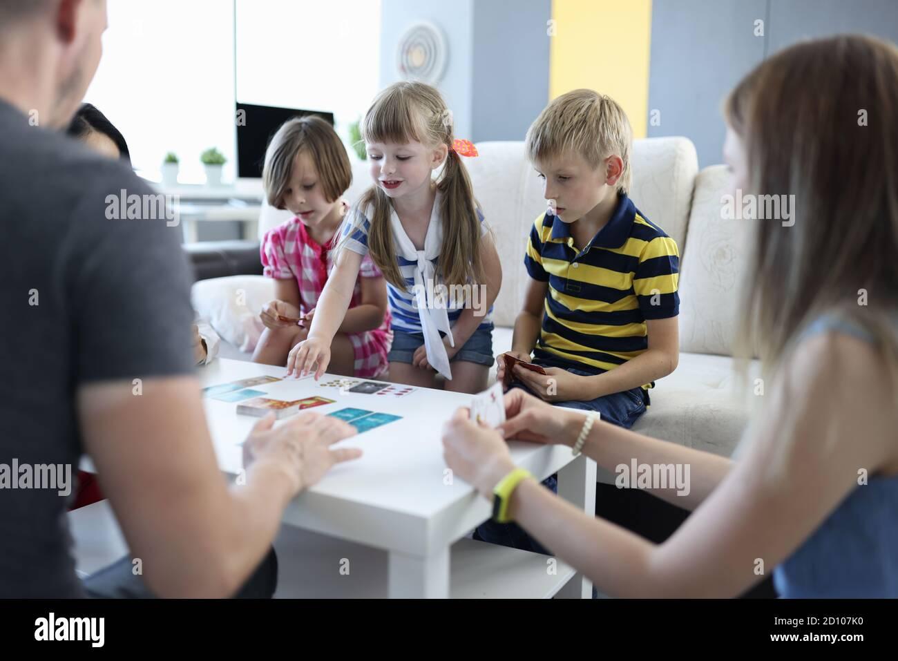Una squadra di tre bambini e una squadra di tre adulti giocano a casa con i giochi da tavolo. Foto Stock