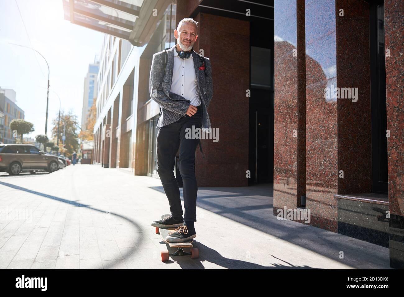 Gioioso anziano che è felice sulla sua longboard Foto Stock