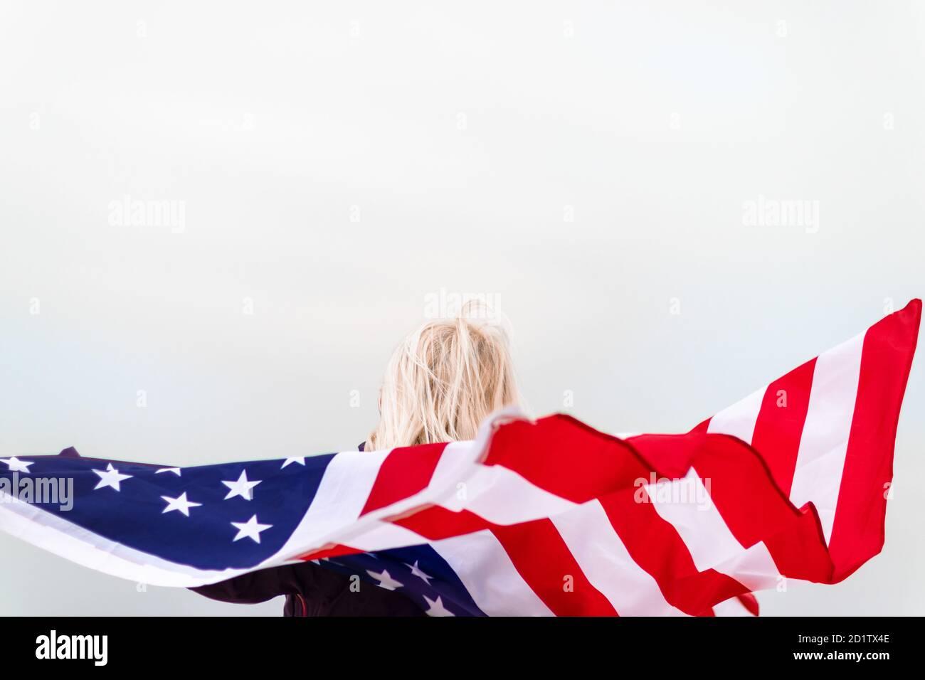 Bionda caucasica che tiene la bandiera americana appoggiata contro la schiena e guardando il mare. Bandiera USA per il giorno dell'indipendenza Foto Stock
