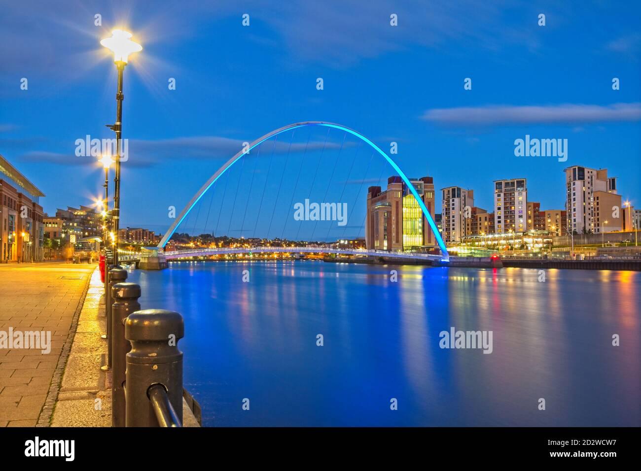 Una vista che guarda lungo il fiume Tyne al tramonto dalla banchina di Newcastle verso il Gateshead Millennium Bridge, il Baltic Arts Center e Gateshead Quays. Foto Stock