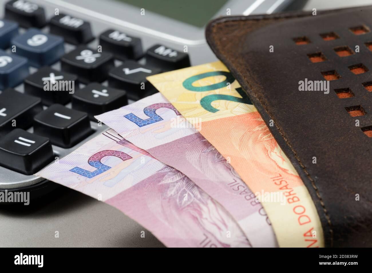 denaro che esce dal portafoglio con calcolatore tascabile sfocato in background. Foto Stock