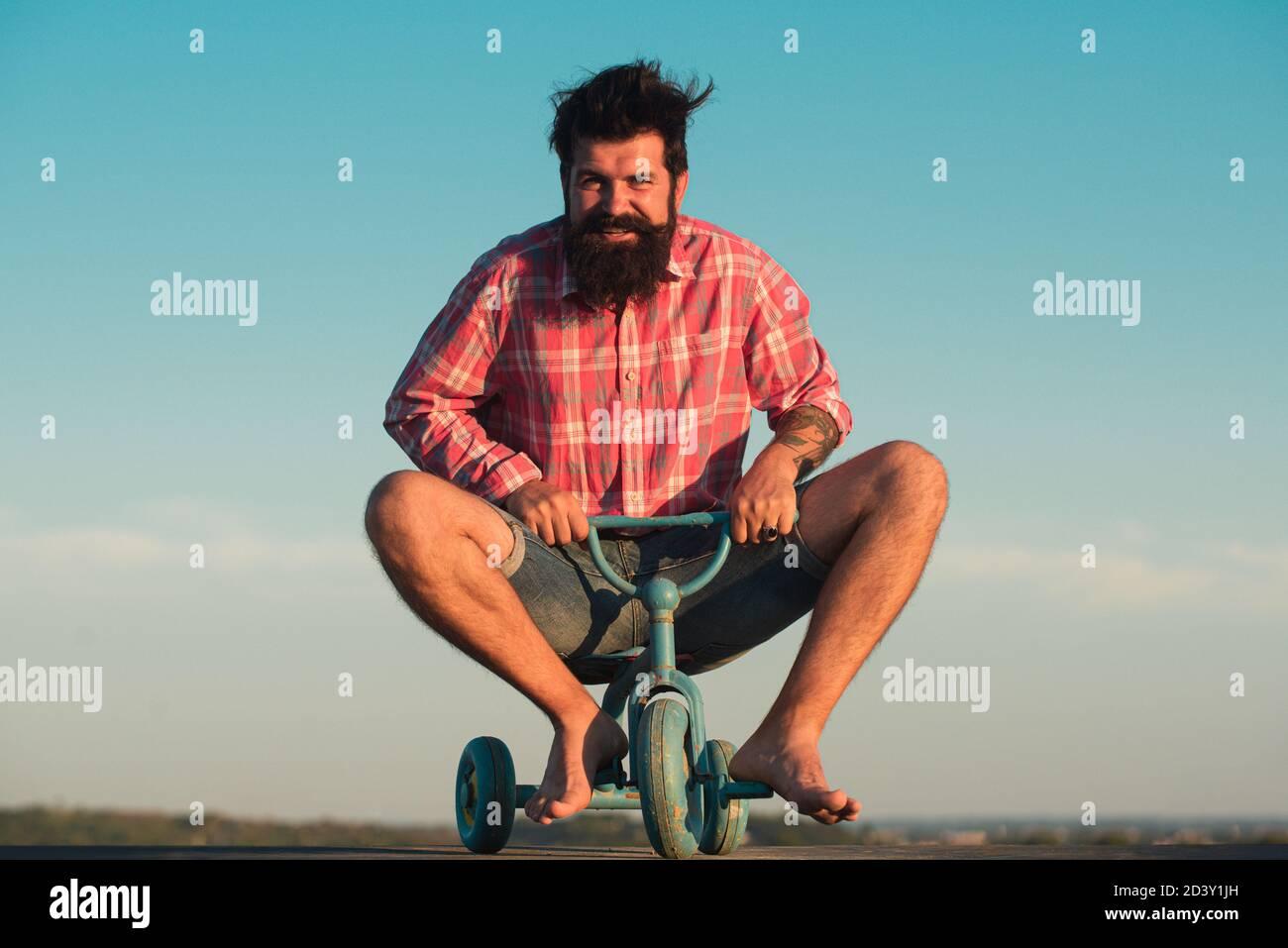 Motociclista divertente. Uomo che guida una piccola bicicletta. Foto Stock
