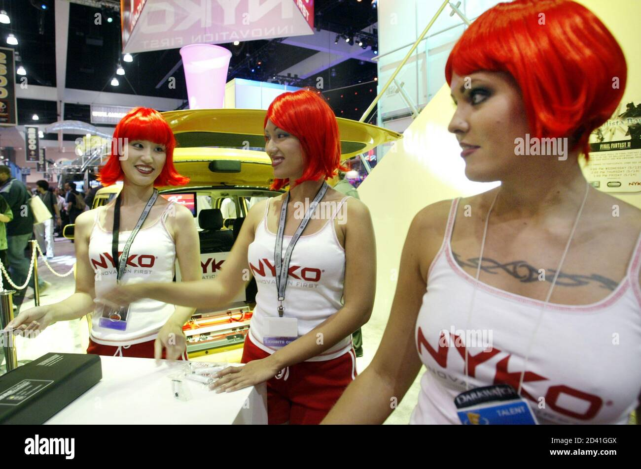 Red headed models Sindy Wei (L), Julie Anne Rose (C) and Letanya Tadlock (R) work the display for Nyko Technologies at the Electronic Entertainment Expo at the Convention Center in Los Angeles May 13, 2004. Nyko Technologies makes peripherals for interactive entertainment, personal computing and consumer electronics products. REUTERS/Robert Galbraith  RG Foto Stock