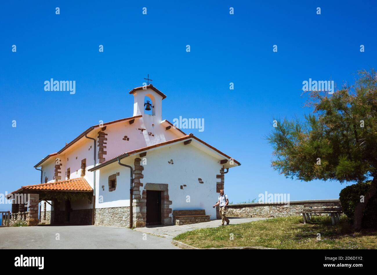 Zumaia, Gipuzkoa, Paesi Baschi, Spagna - 15 luglio 2019 : UN uomo passa accanto alla piccola cappella di San Telmo dedicata al santo patrono dei marinai. Foto Stock