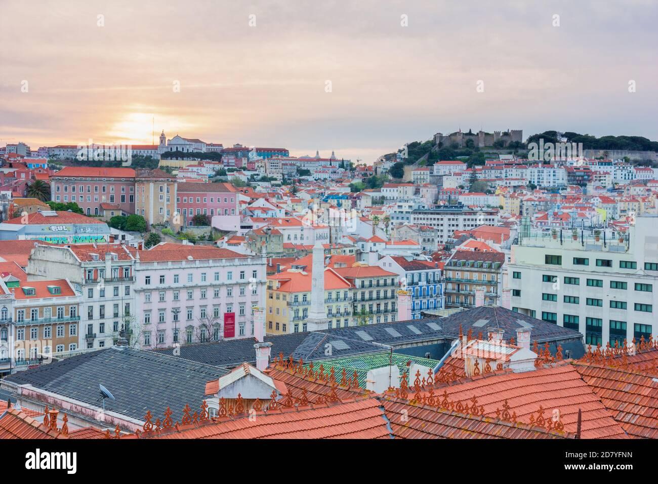 Vista delle belle e colorate case dall'alto durante l'alba con il cielo arancione e rosa a Lisbona, Portogallo. Foto Stock