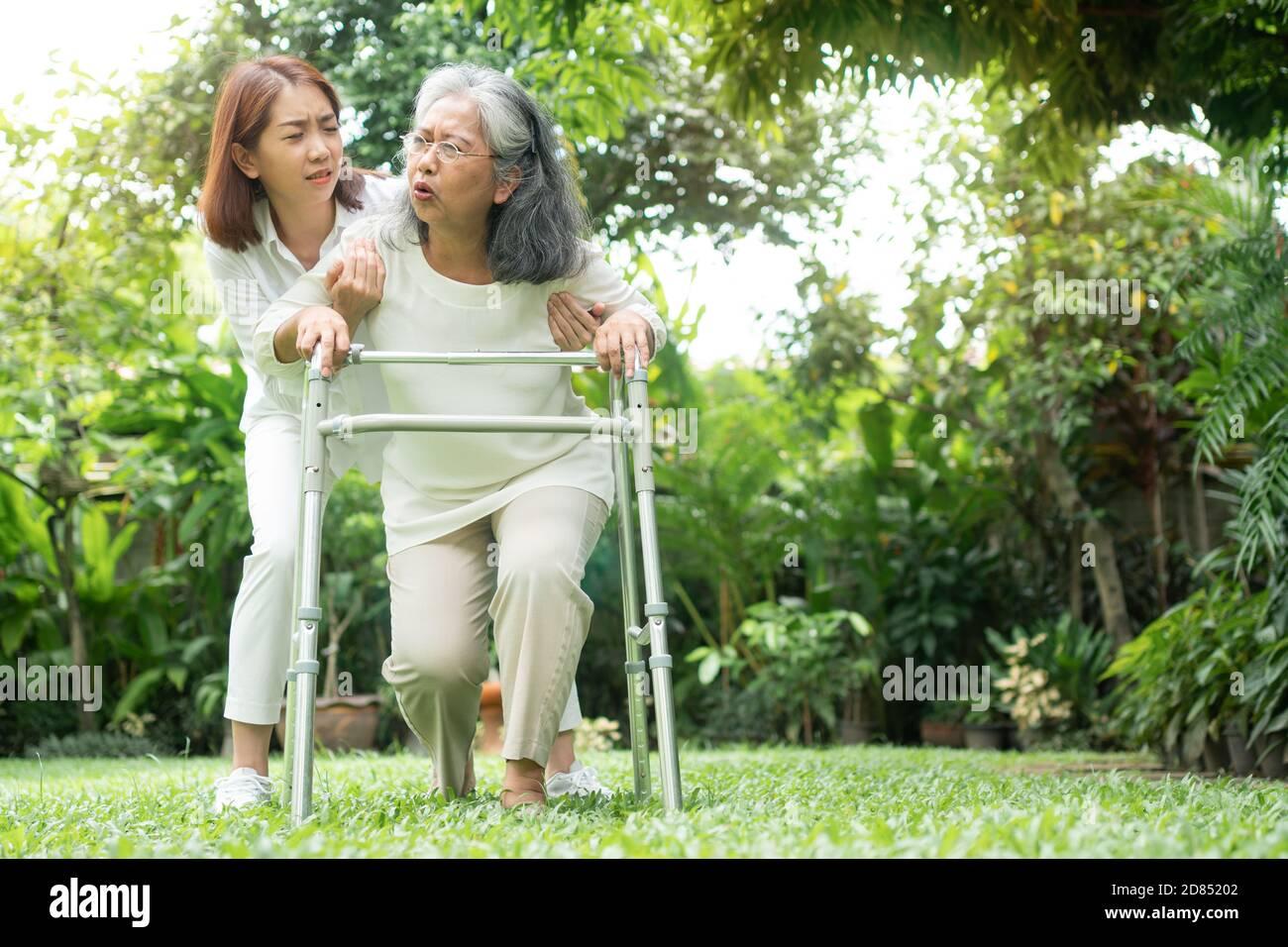 Donna anziana asiatica che cade a casa nel cortile causato da miastenia (debolezza muscolare) e la figlia è venuto per aiutare il sostegno. Concetto di vecchio e Foto Stock