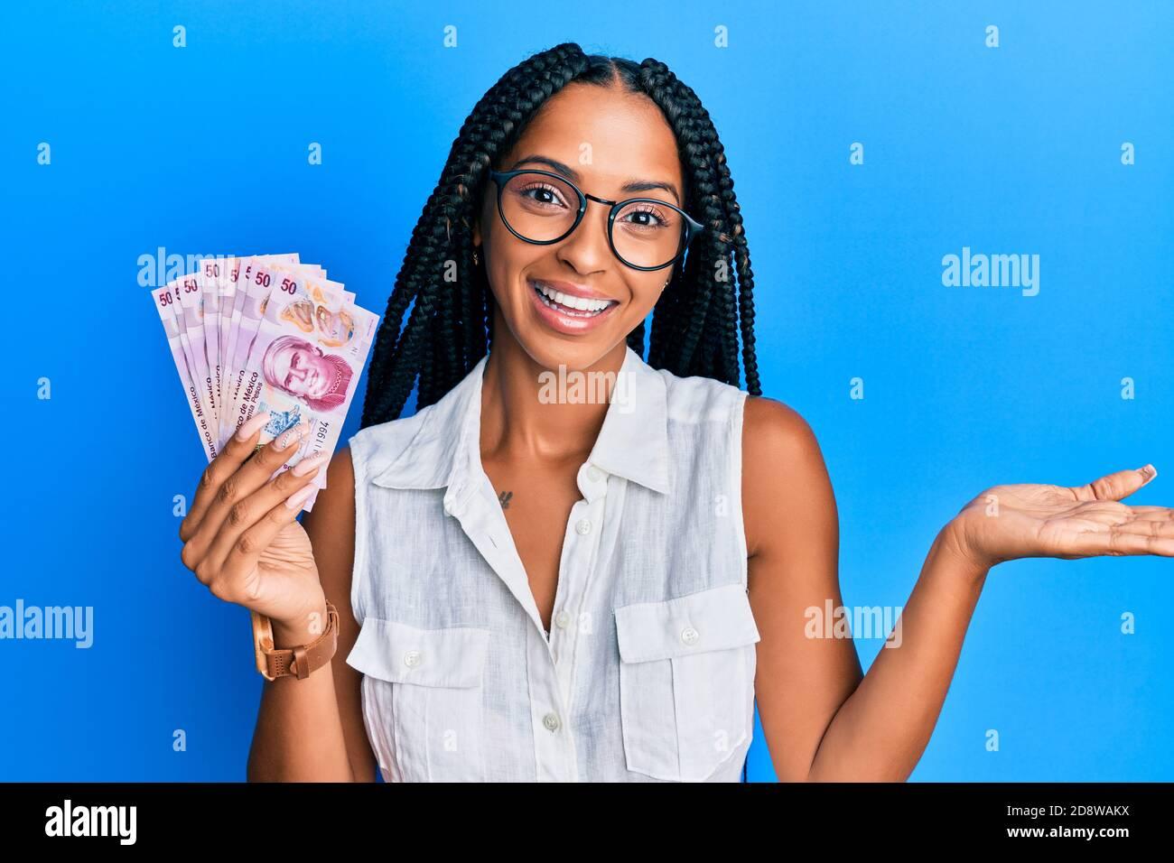 Bella donna ispanica in possesso di 50 pesos messicani banconote celebrare il successo con sorriso felice e espressione vincente con mano sollevata Foto Stock