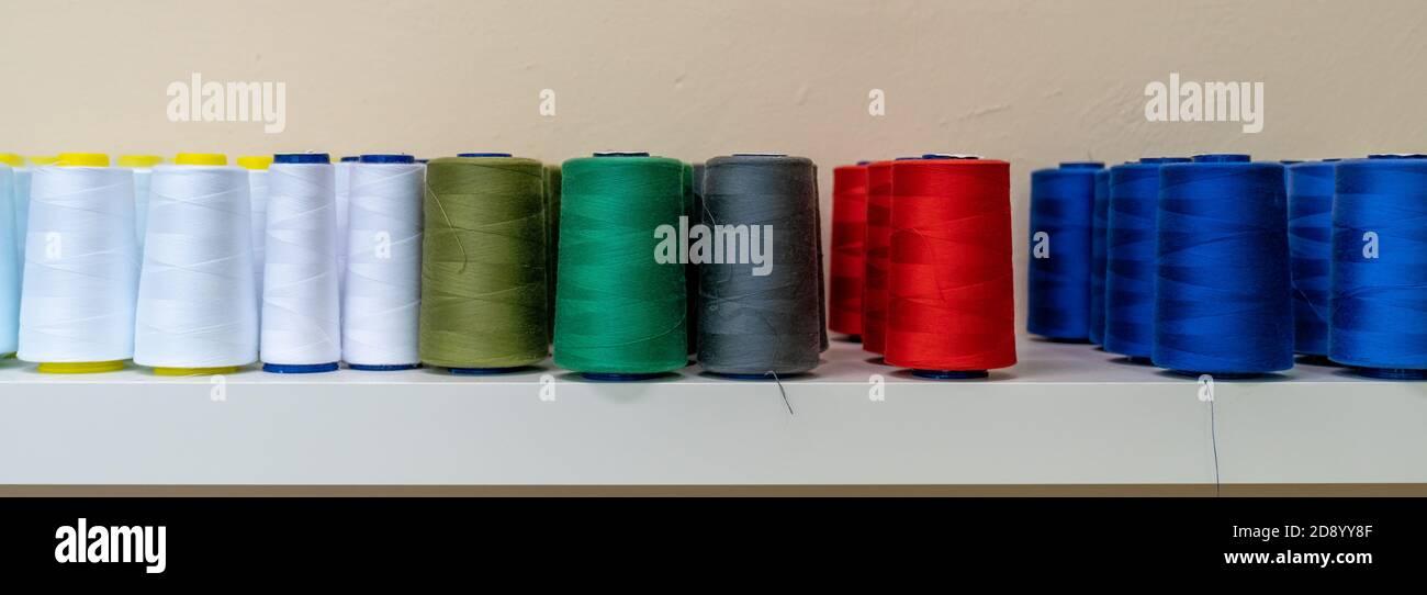fili colorati per la macchina da cucire sul ripiano, striscione Foto Stock