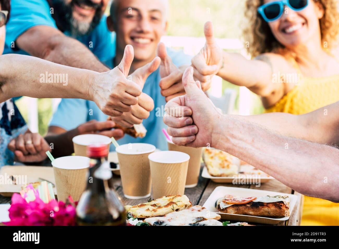 Gruppo famiglia caucasica persone celebrare insieme con divertimento e gustando cibo e bevande -. Festa di compleanno primo piano con pollici in su e risate in backgr Foto Stock