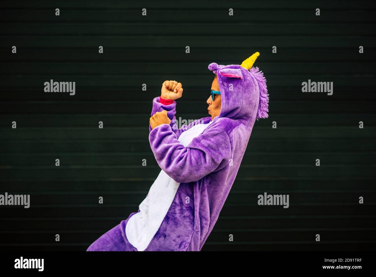 Crazy unicorn maschera danza con la gente divertente - allegro felice donna che balla con abito da carnevale con parete nera sullo sfondo - Divertimento e felicità concep Foto Stock