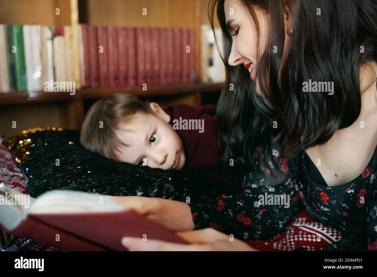 Una giovane donna legge un libro a un bambino. Una madre insegna al suo ragazzino di leggere. Foto Stock