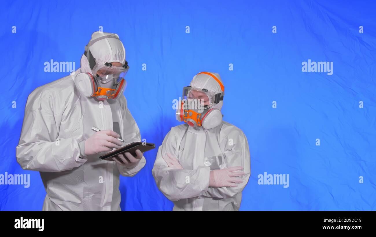 Lo scienziato virologo in respiratore scrive in un computer tablet con stilo. Uomo e donna che indossano una maschera medica protettiva. Tasto Chroma blu. Foto Stock