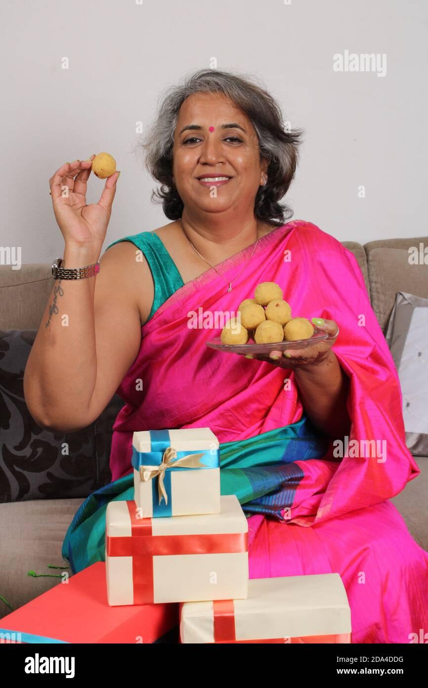 Donna indiana in saree / sari con laddu e confezioni regalo su diwali / festival. Foto Stock