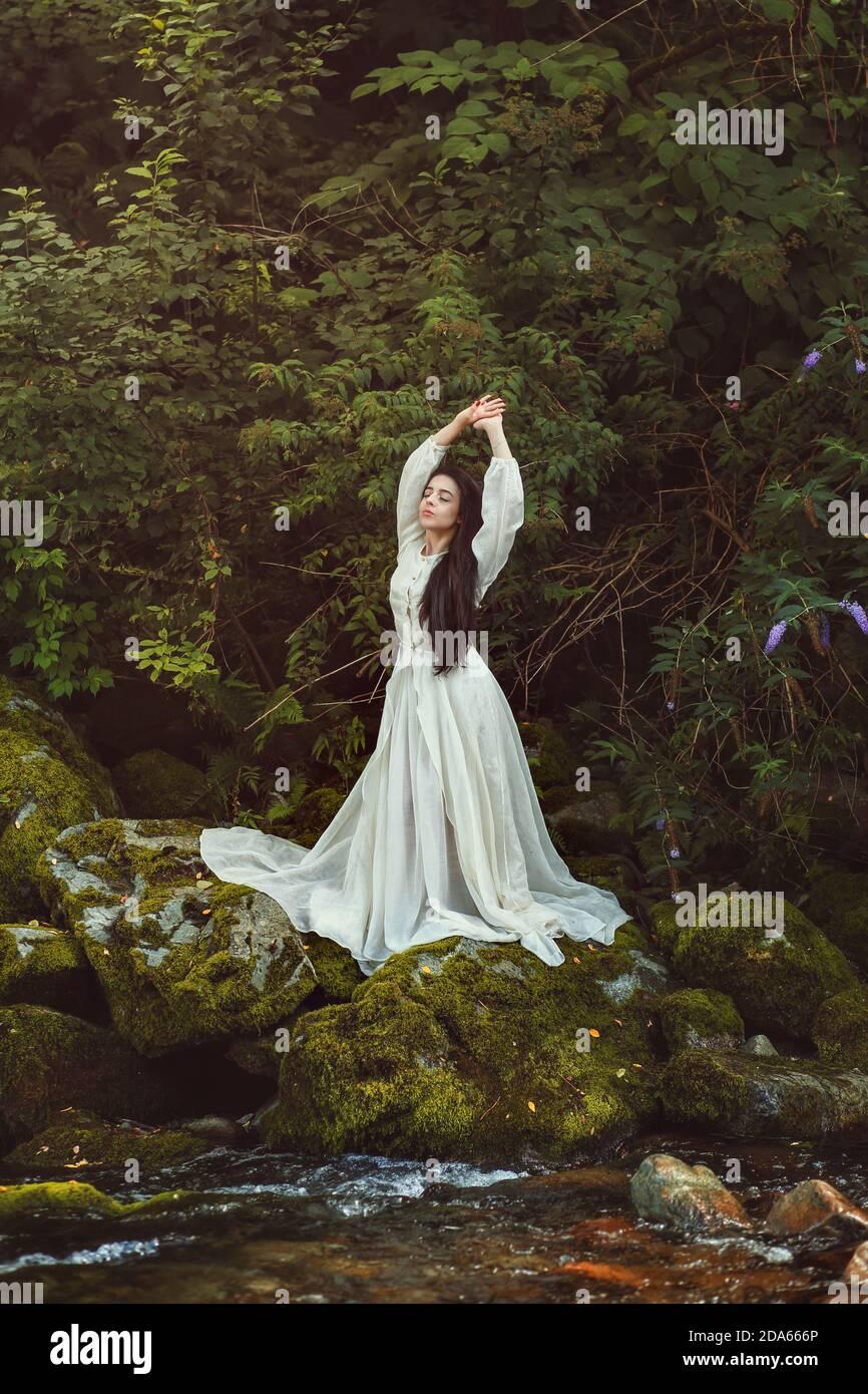 Bella donna romantica in posa tra foglie verdi Foto Stock