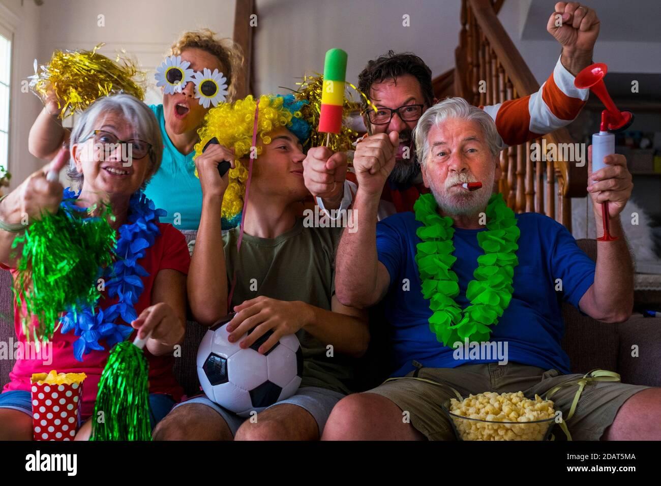 Gruppo di pazzi e colorati sostenitori del calcio festeggiano e esultano durante la partita - età miste della famiglia caucasica e gli amici godono di sport su Foto Stock