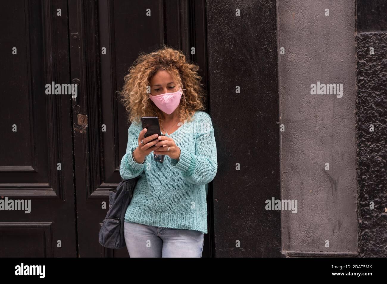 Donna adulta indossare maschera di protezione contro l'emergenza del virus del coronavirus covid-19 - proteggiti le persone con l'accessorio antivirus - femmina in città Foto Stock