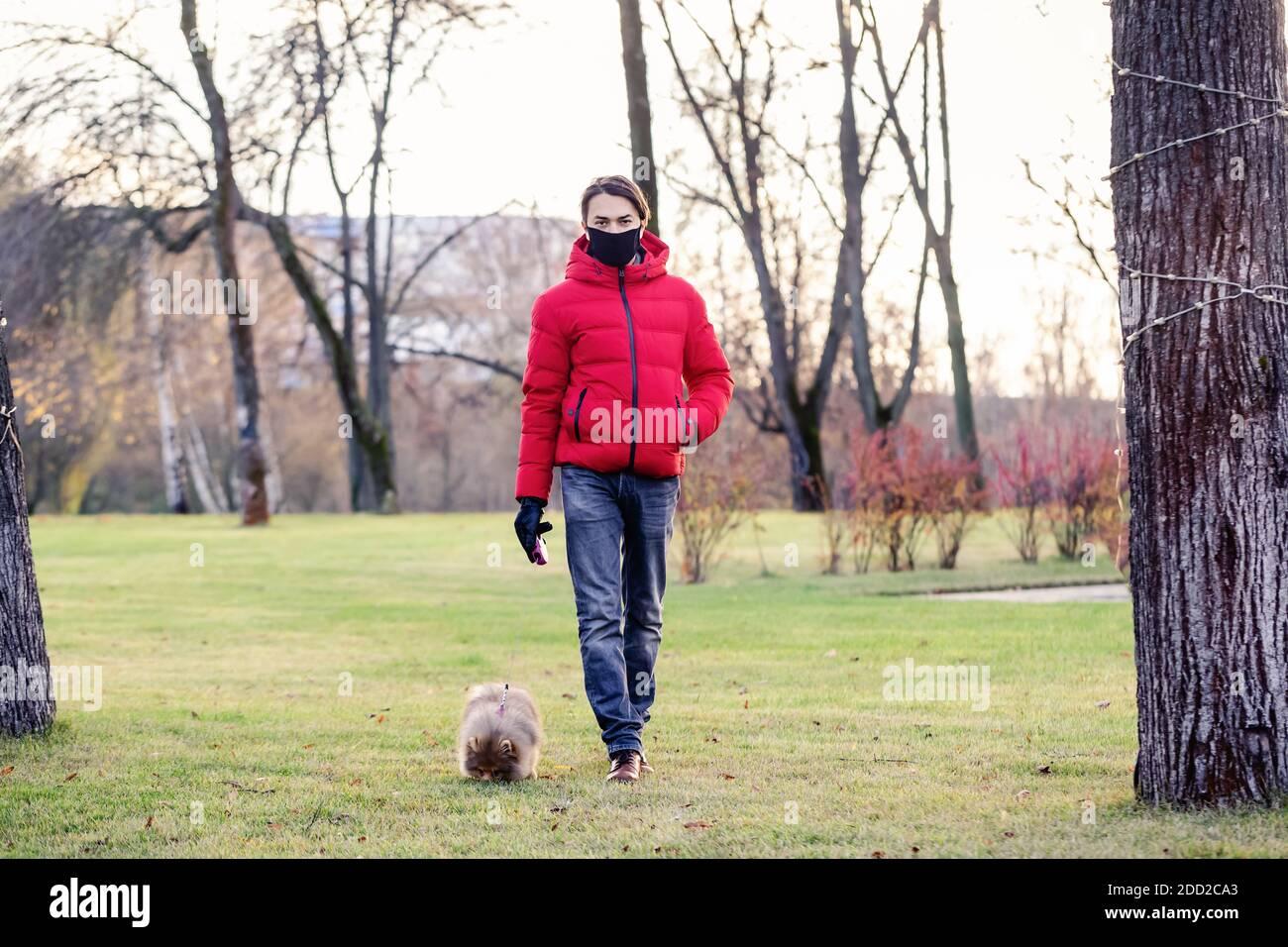 L'uomo con maschera facciale prende il suo cane per una passeggiata vicino a casa durante il coronavirus. Si prende cura del suo animale domestico. Brevi passeggiate durante il coronavirus. Quarantena con un Foto Stock