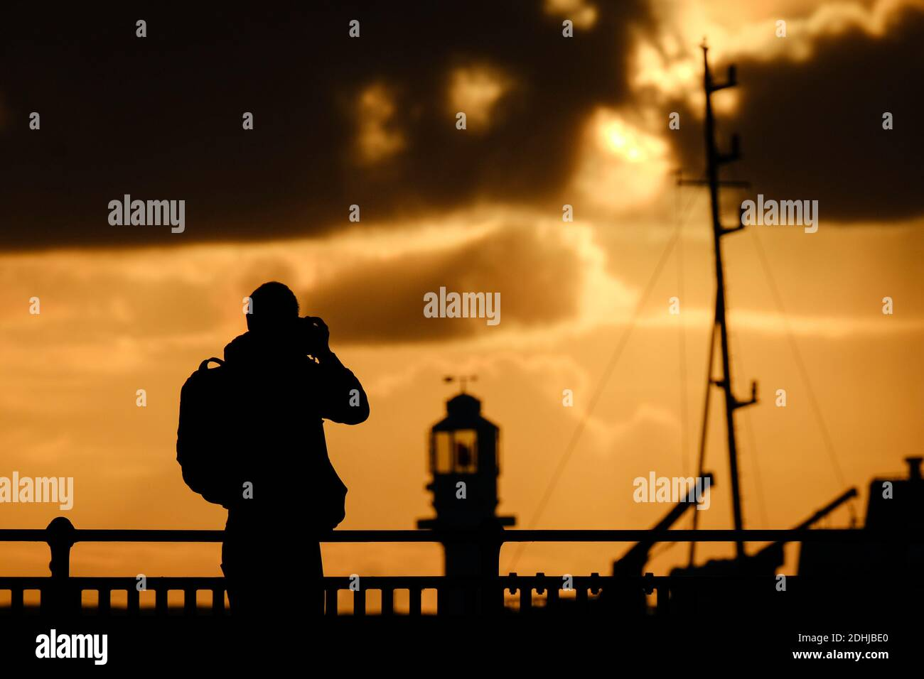 Un fotografo cattura la calma prima di Storm Alex, mentre il sole sorge dietro il faro del porto di Penzance il primo giorno di ottobre. Foto Stock