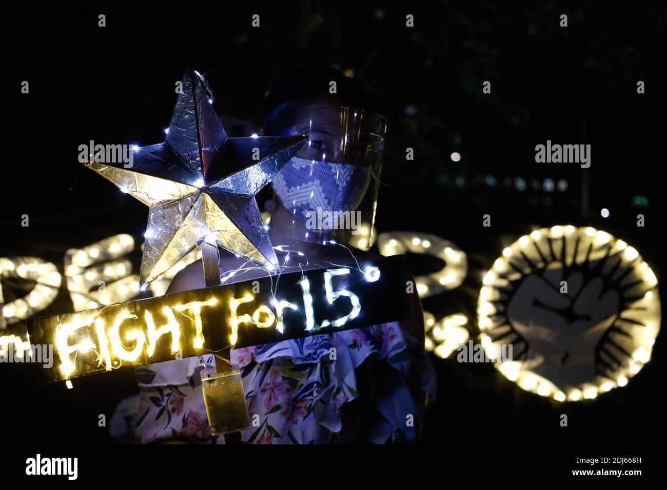 Gli attivisti del clima hanno acceso le candele e hanno tenuto striscioni di illuminazione a LED l'11 dicembre 2020. Questa attività commemora il quinquennio dell'accordo di Parigi con un invito a lottare per il 1.5 e a porre fine all'uccisione dei difensori dell'ambiente. Quezon City, Filippine. Foto Stock