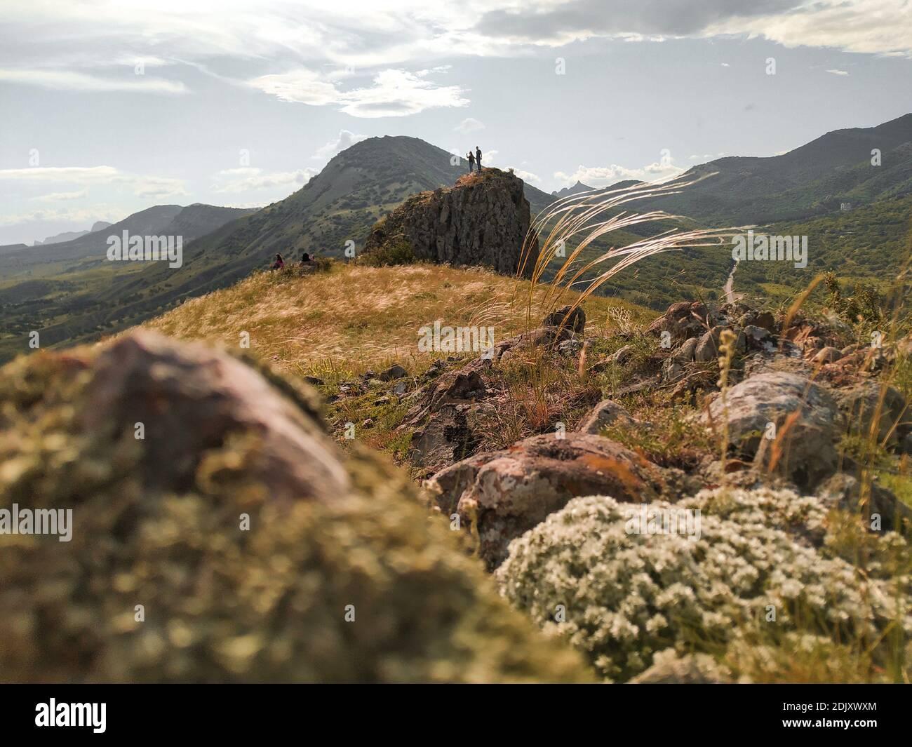 Paesaggio estivo con una coppia che guarda il paesaggio sulla roccia. Destinazioni di viaggio e obiettivi escursionistici raggiungimento per una buona salute e corpo forte Foto Stock