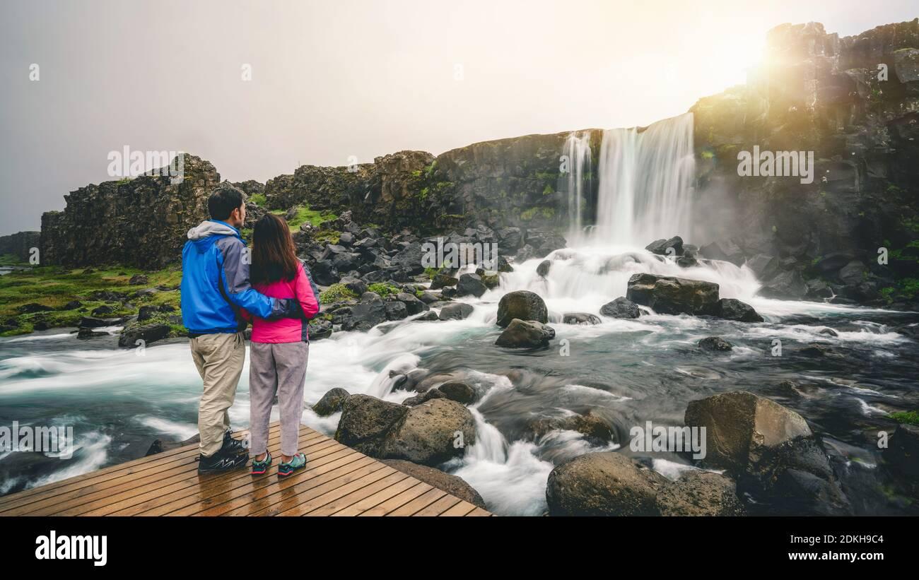 Accoppiare i viaggiatori viaggiare a cascata Oxararfoss a Thingvellir National Park, Islanda. Cascata Oxararfoss è famosa cascata attira turisti per Foto Stock
