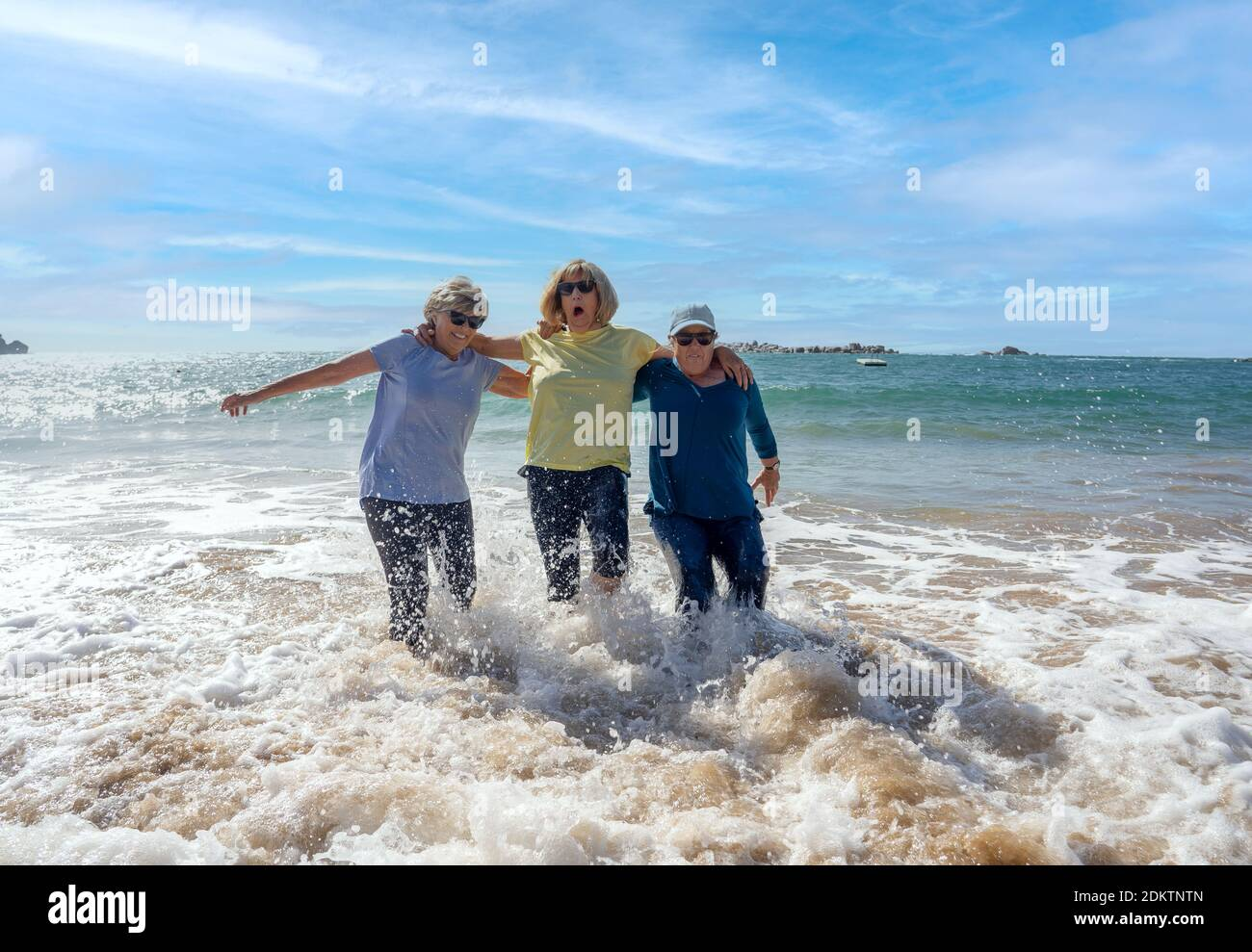Gruppo di donne anziane in pensione sui loro anni '60 e '70 cadendo in acqua divertirsi sulla spiaggia. Le Signore più anziane ridono mentre cadono giù perdendo balan Foto Stock