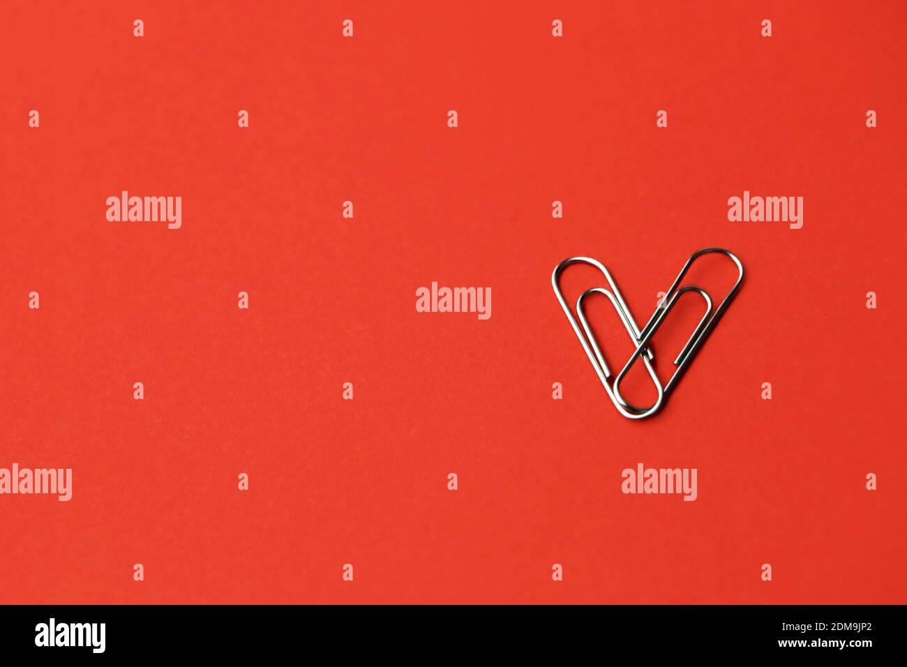 La carta a forma di cuore si aggancia su uno sfondo rosso. Concetto di San Valentino. Foto di alta qualità Foto Stock