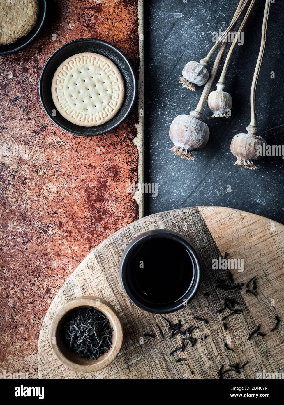 Diversi tipi di biscotti e tazza di caffè su sfondo grigio e teracota. Scatto in testa. Foto Stock