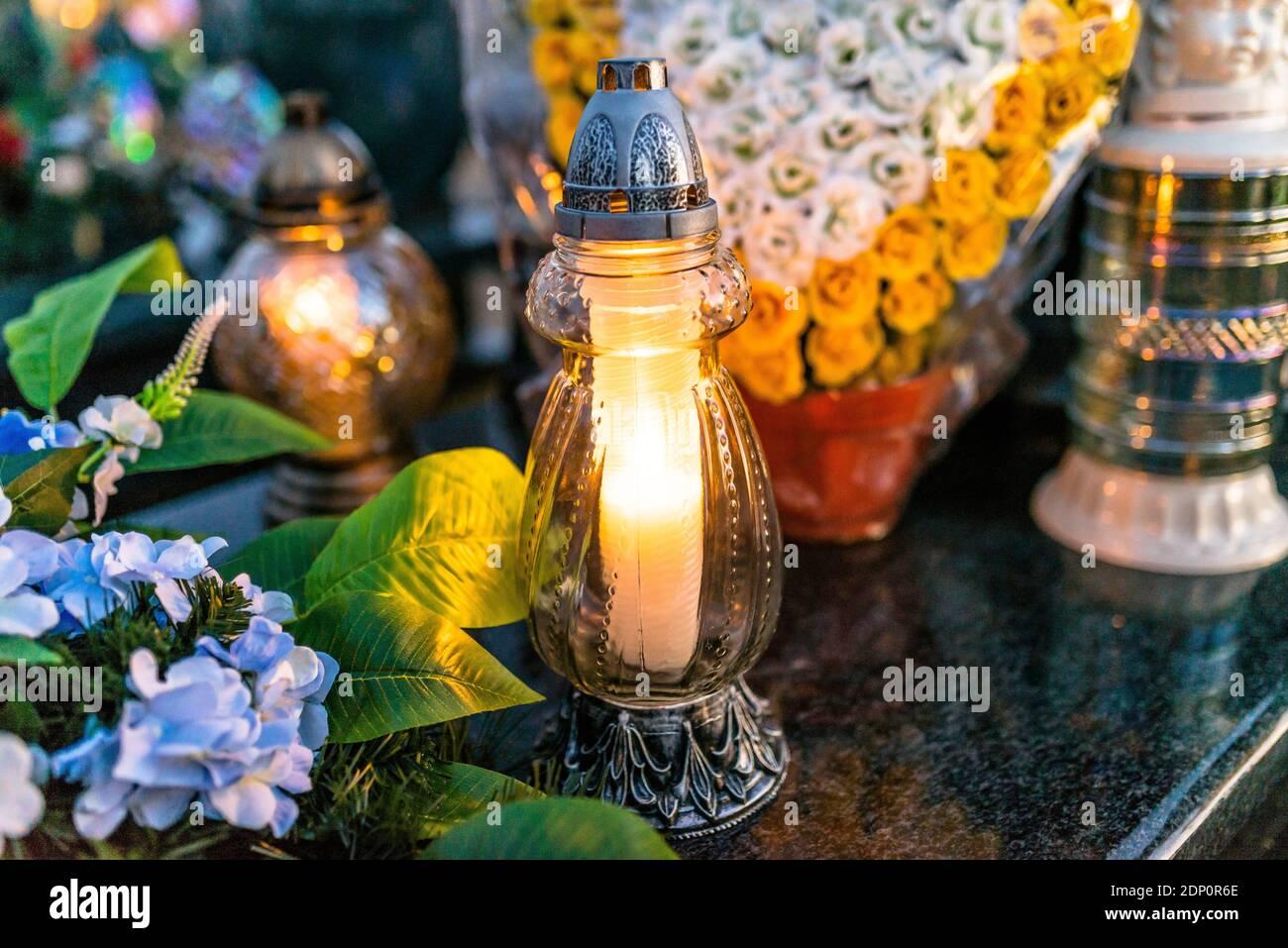 Fiori artificiali e candelabri giacciono sulla Tombstone nel Cimitero. Foto Stock