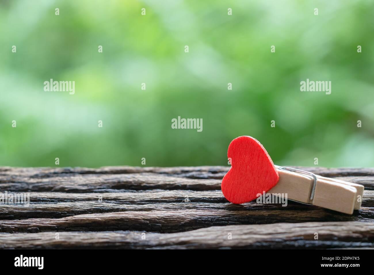 Primo piano fuoco selettivo delle clip di carta di legno di cuore rosso con sfondo verde della natura e spazio di copia. Ideale per giorno di San Valentino, Amore e concetto di relazione. Foto Stock