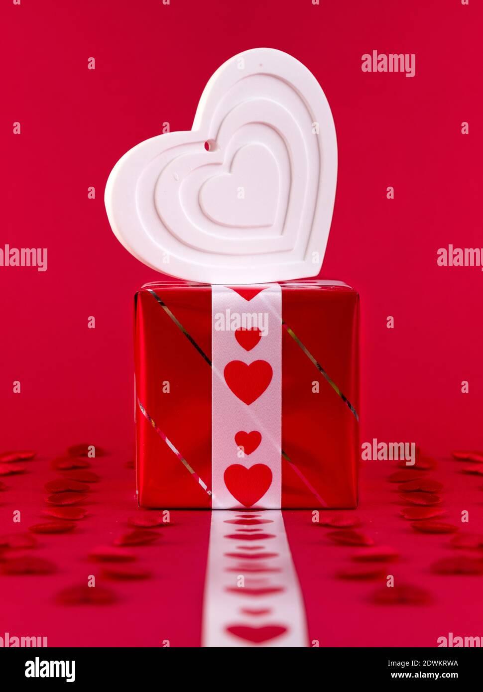 Forma bianco cuore su confezione regalo su sfondo rosso Foto Stock
