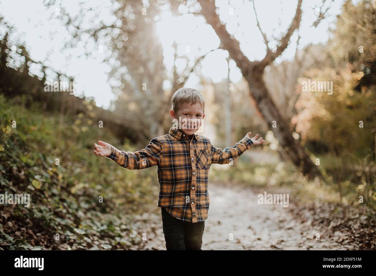 Ragazzo spensierato in piedi con le braccia distese in foresta Foto Stock