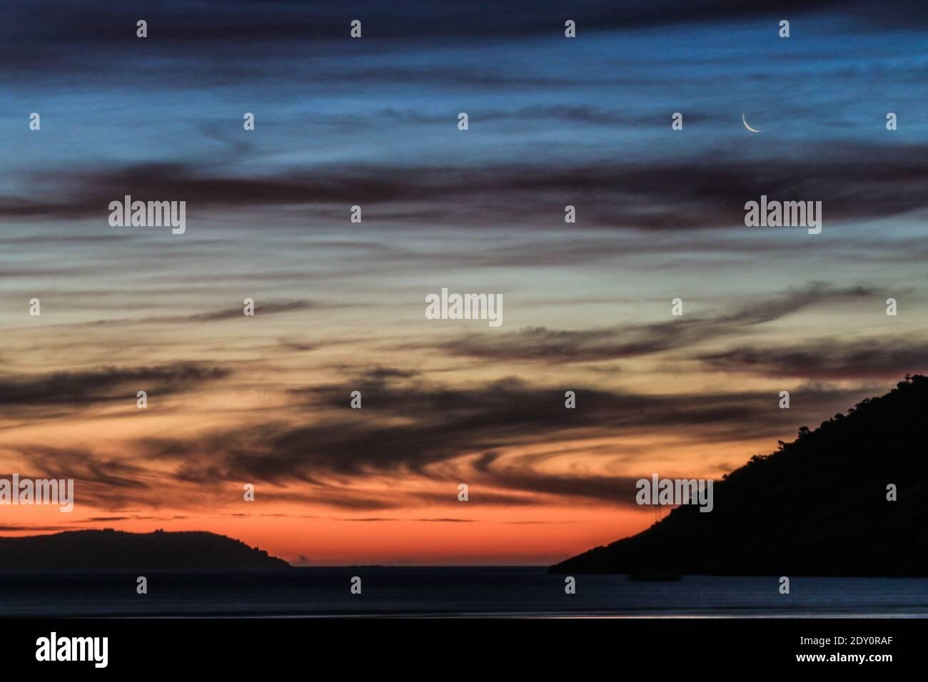 Vista panoramica del mare contro il cielo drammatico durante il tramonto Foto Stock