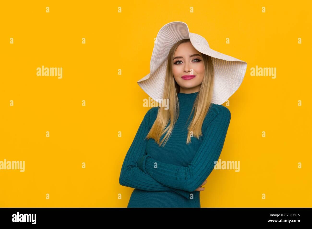 Bella giovane donna in cappello bianco sole e maglione teal è in posa con le braccia incrociate. Girata in studio su sfondo giallo. Foto Stock