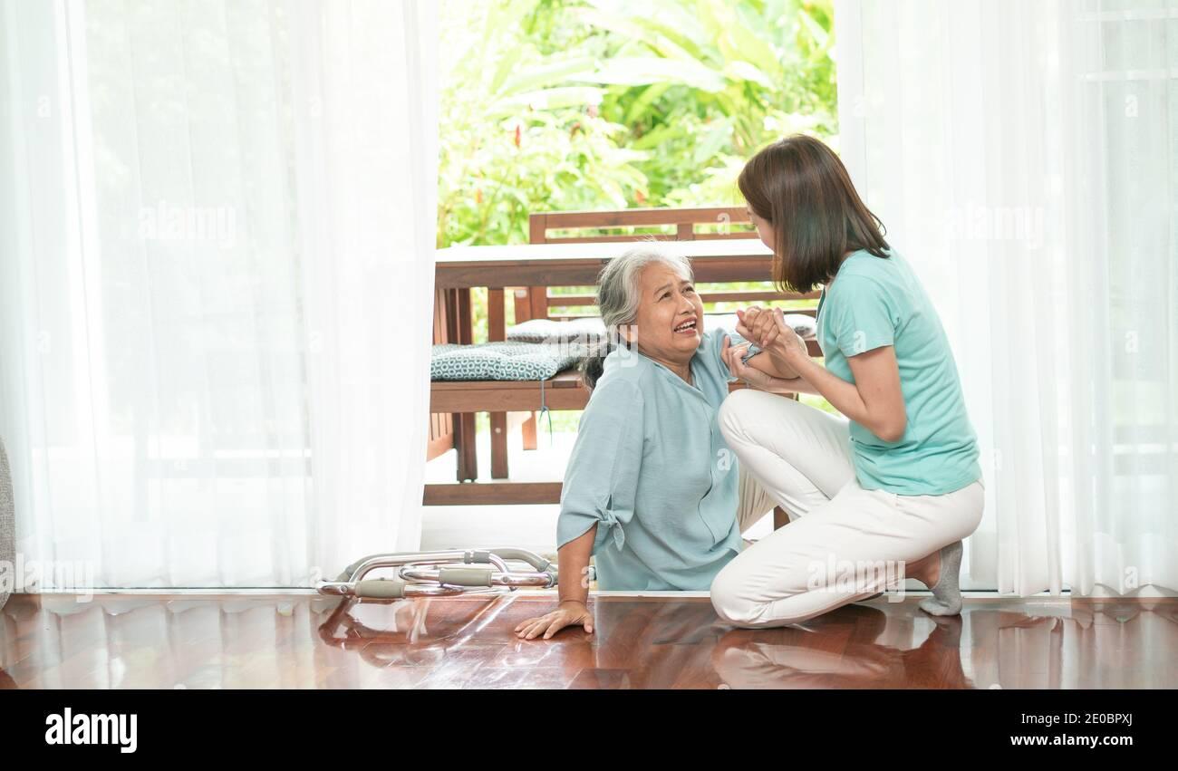 Donna anziana asiatica che cadde sul pavimento sdraiato a casa dopo che si è inciampata alla soglia e gridando nel dolore e l'infermiera è venuto per aiutare il sostegno. Concetto o Foto Stock