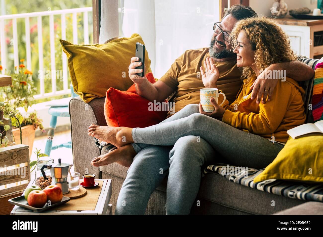Adulto felice coppia uomo e donna a casa godersi la mattina colazione e videochiamata ad amici o genitori - gente caucasica allegra acti indoor Foto Stock
