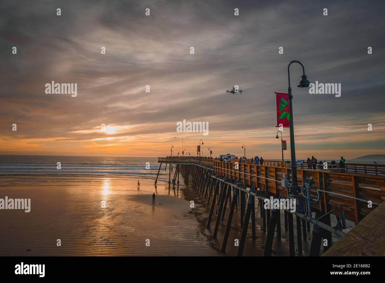 Pismo Beach, California, USA - 1 gennaio 2021 Tramonto sulla spiaggia e sul molo. Un iconico molo in legno della California lungo 370 metri nel cuore del Pismo Foto Stock