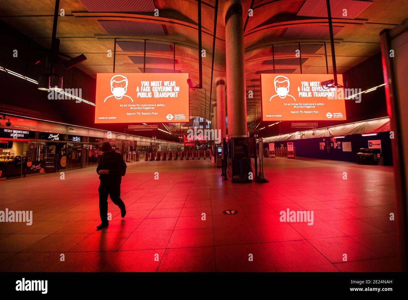 Una persona solitaria nell'atrio della stazione della metropolitana di Canary Wharf durante l'ora di punta di Londra, mentre continua il terzo blocco nazionale dell'Inghilterra per frenare la diffusione del coronavirus. Foto Stock