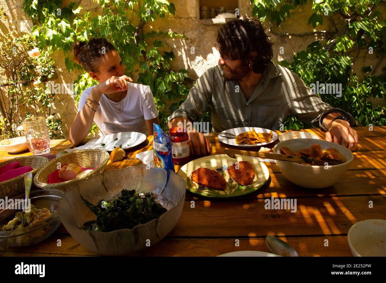 Una giovane coppia che gusta un pasto mediterraneo. Foto Stock