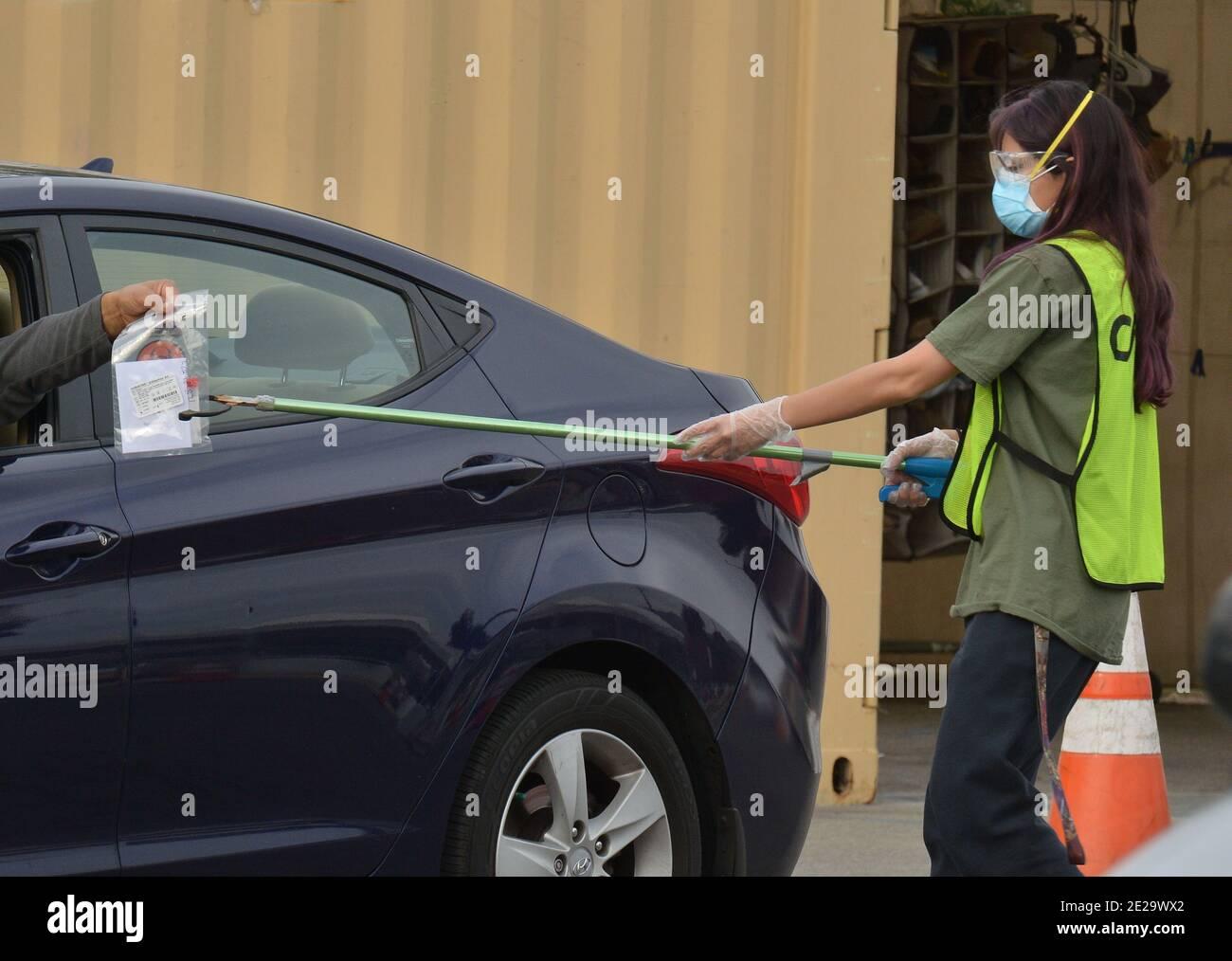 """Los Angeles, California, Stati Uniti. 13 gennaio 2021. Los Angeles, Stati Uniti. 13 gennaio 2021. I residenti depositano il loro test curativo del coronavirus in un ricettacolo presso il sito di test della diga di Hansen a Los Angeles martedì 12 gennaio 2021. I funzionari sanitari della contea di Los Angeles hanno dichiarato che domenica smetteranno di fornire il test del coronavirus comunemente utilizzato dopo che le autorità federali hanno sollevato domande sulla sua accuratezza, affermando che il test effettuato da Curative comporta un """"rischio di risultati falsi, in particolare risultati falsi negativi"""". Photo by Jim Ruymen/UPI Credit: UPI/Alamy Live News Credit: UPI/Alamy Live News Foto Stock"""