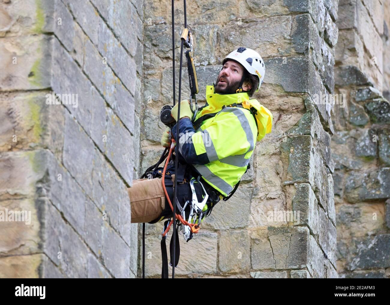 Stonemason James Preston da SSH Conservation, ascili da Rievaulx Abbey nel Nord Yorkshire come l'inglese Heritage si prepara a svolgere vitale lavoro di conservazione. English Heritage commissiona un'indagine all'abbazia di Rievaulx su un ciclo di cinque anni per valutare la condizione dell'abbazia dal piano terra fino alla cima della struttura. Foto Stock