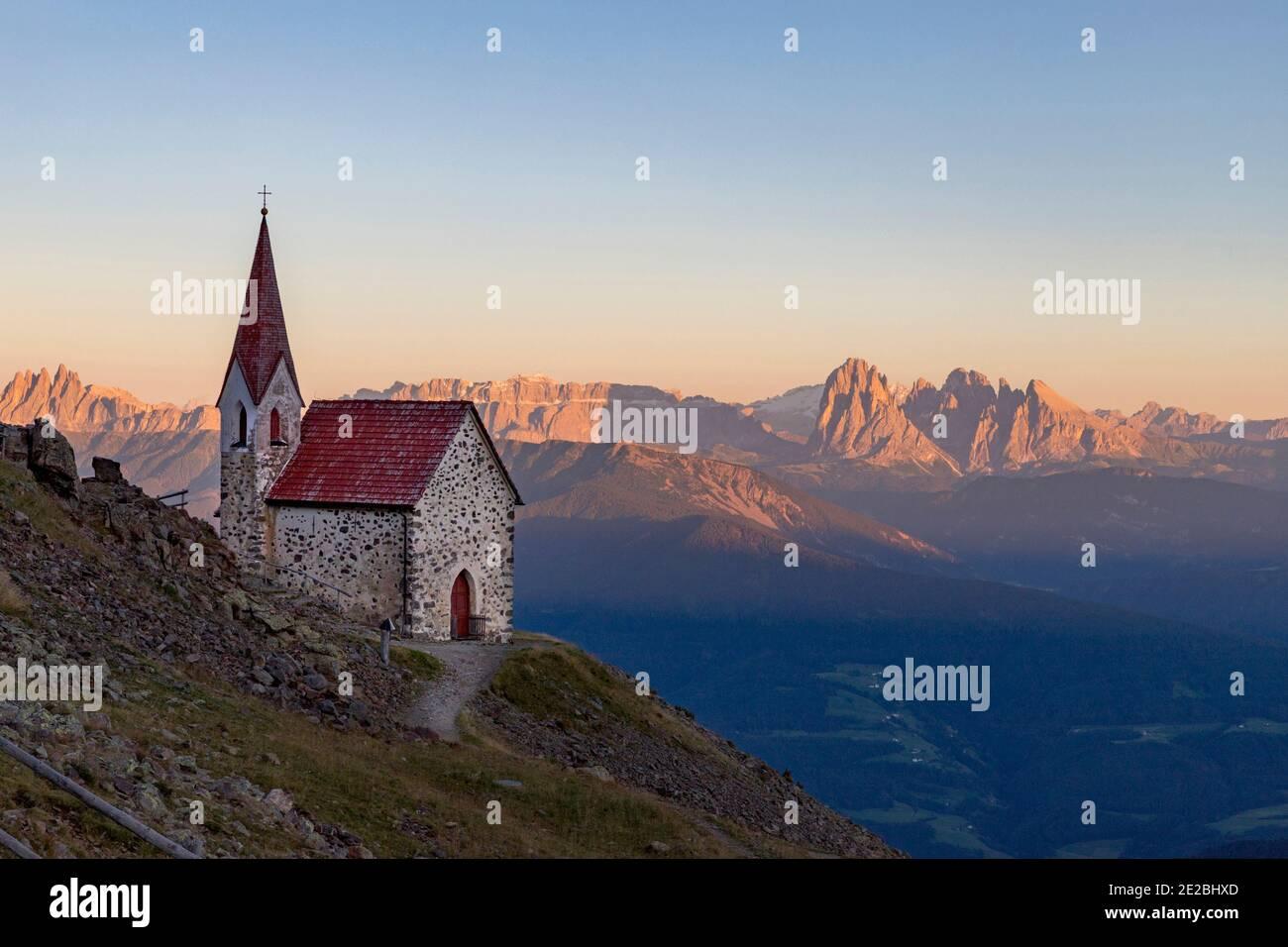 Piccola cappella e vista sulla catena montuosa delle Dolomiti illuminate d'arancio al tramonto d'estate, Alto Adige, Italia Foto Stock