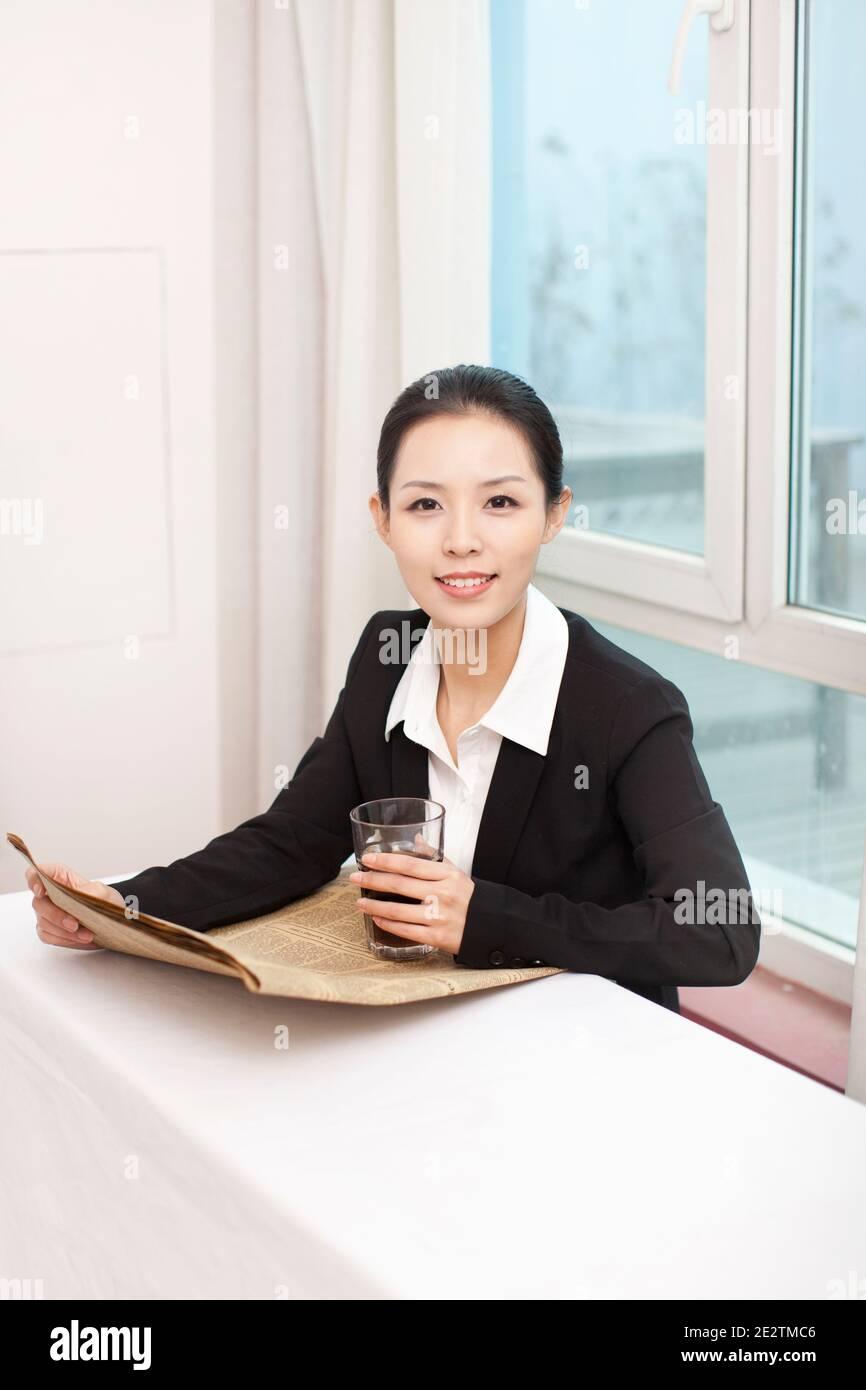 Giovane donna di affari che tiene il giornale alla scrivania foto di alta qualità Foto Stock
