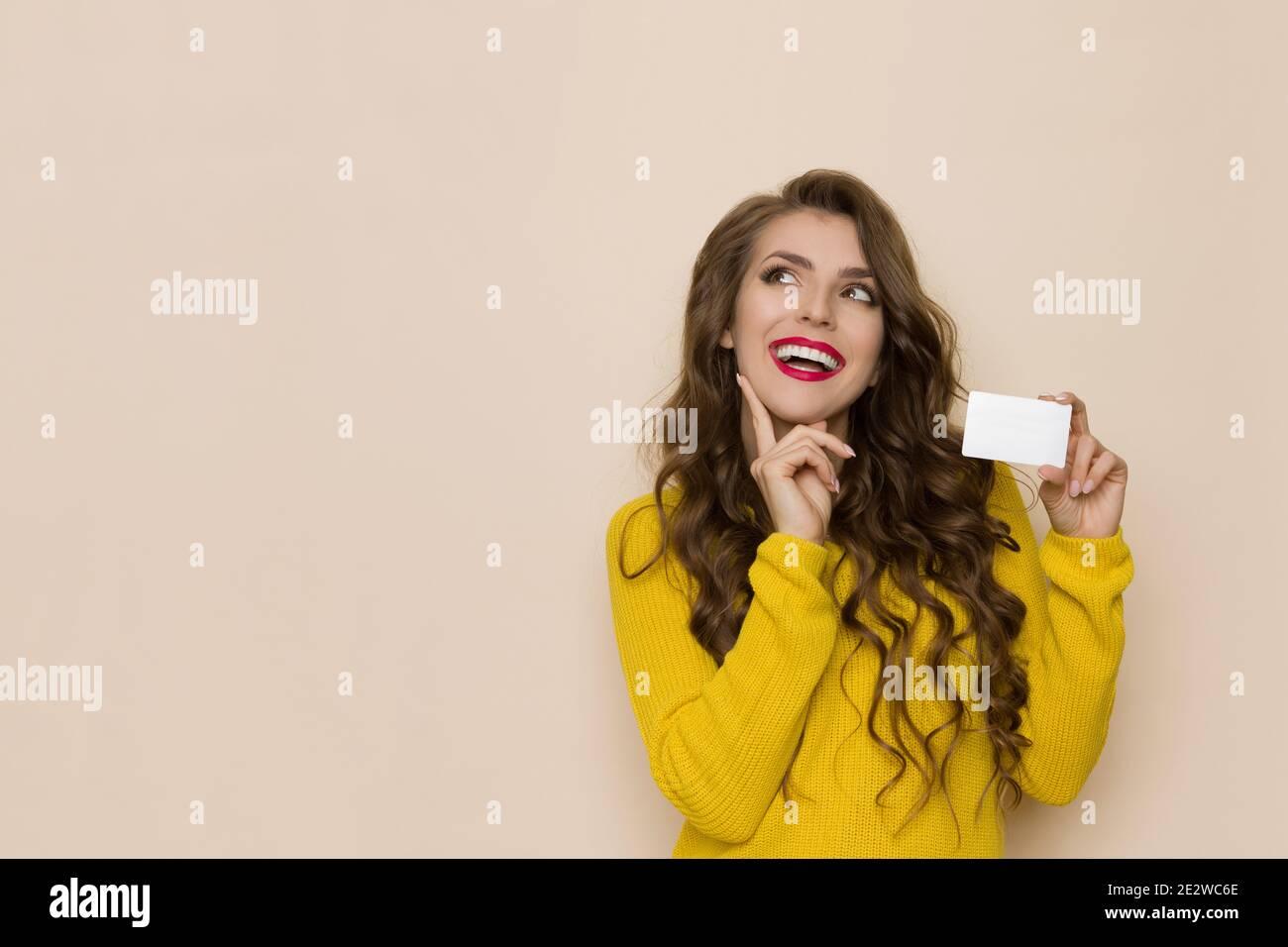 Casual giovane donna sta tenendo carta di plastica bianca, sorridente, guardando in su e pensando. Girata in casa su sfondo beige. Foto Stock