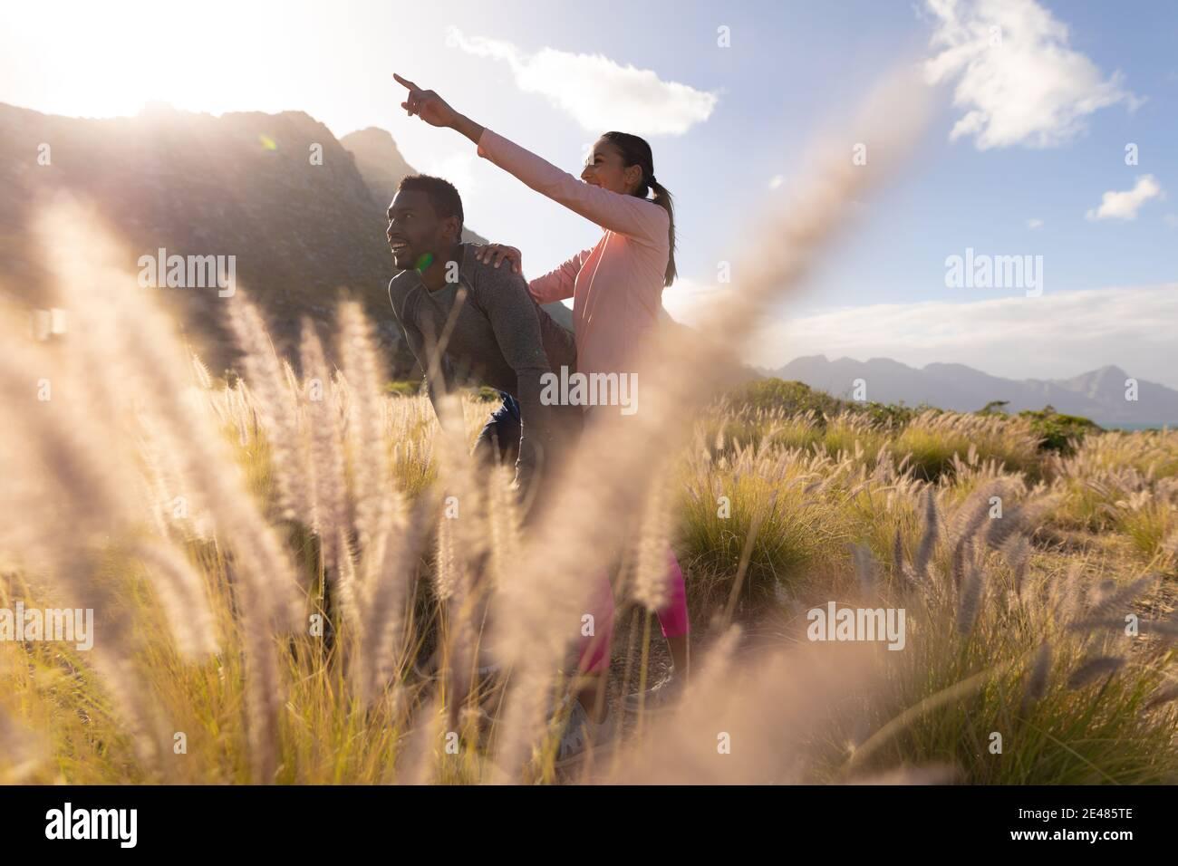 Calzare la coppia afroamericana in un abbigliamento sportivo poggiato sulle ginocchia in erba alta Foto Stock