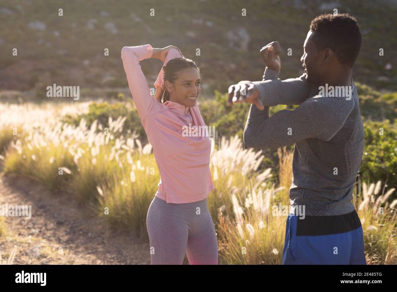 Adatta la coppia afroamericana in abbigliamento sportivo che si allunga in erba alta Foto Stock