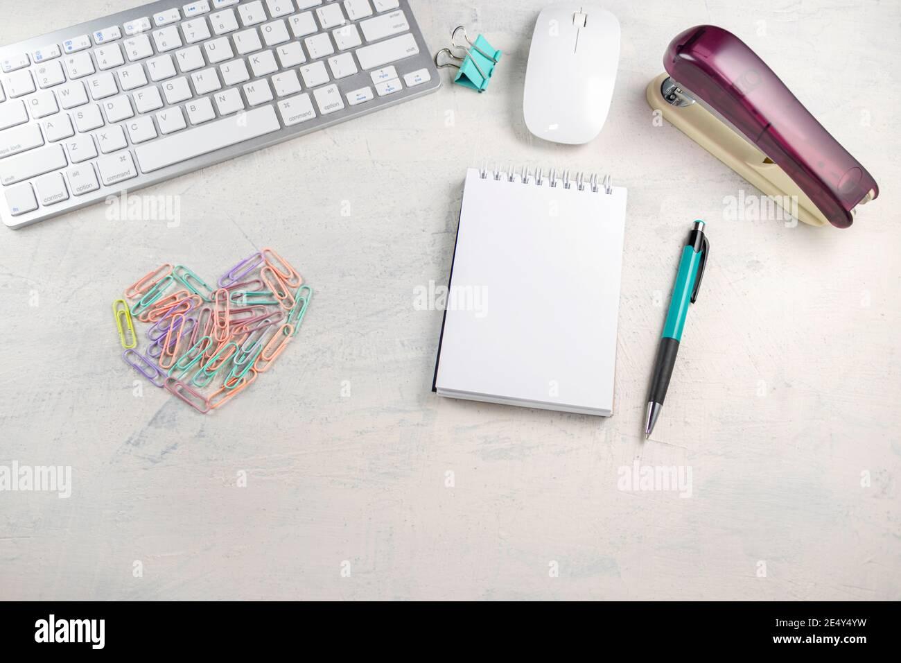 Graffette colorate sotto forma di cuore su un desktop con un blocco note vuoto per la scrittura. San Valentino in ufficio. Vista dall'alto Mock-up Foto Stock