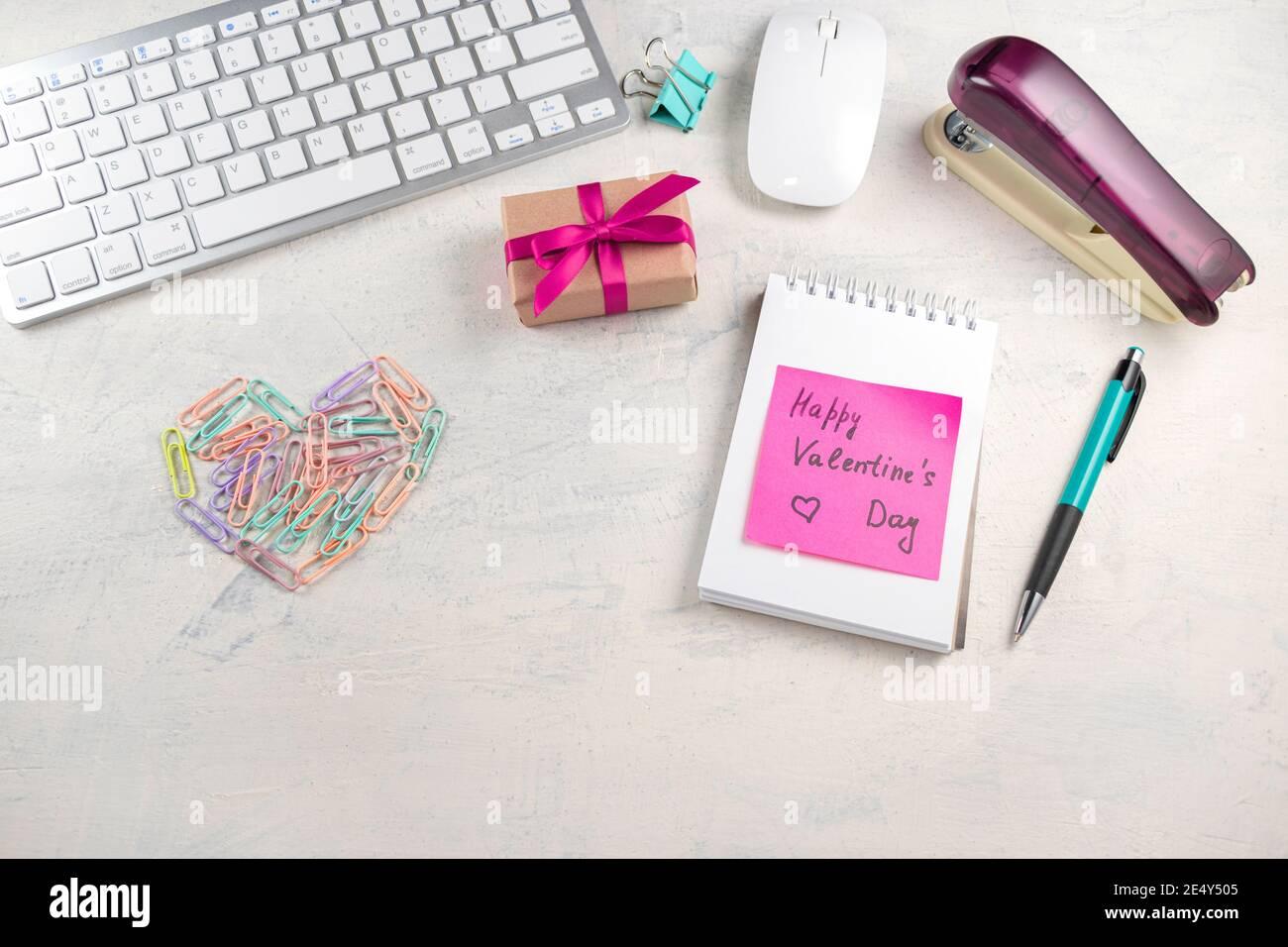 Parole buon San Valentino in una nota sul desktop con clip di carta colorata a forma di cuore e regalo con nastro rosso. San Valentino in offerta Foto Stock