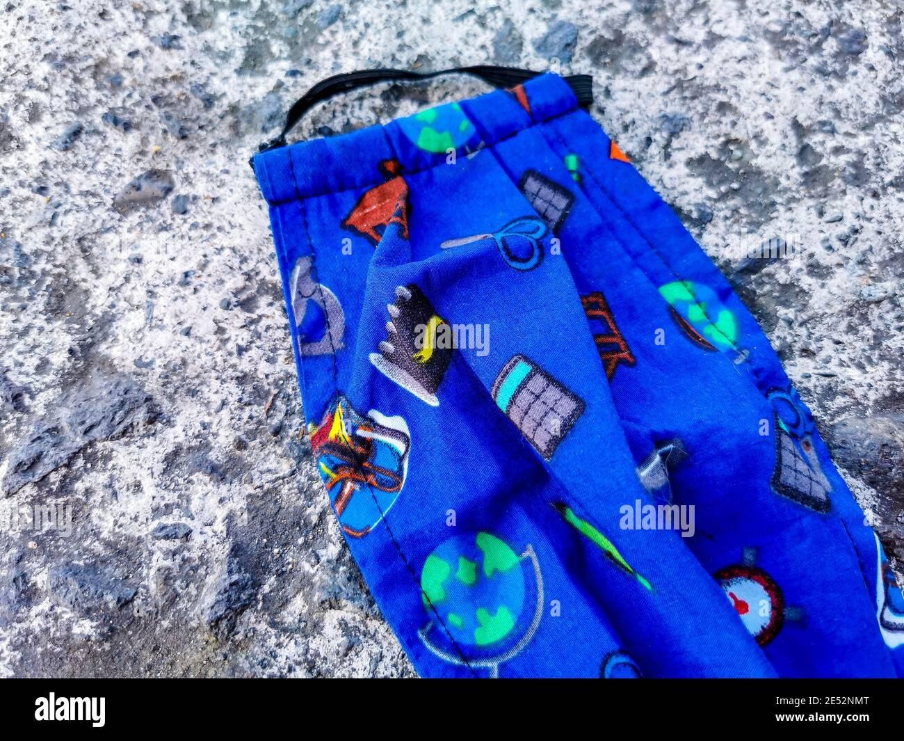 Maschere colorate blu per bambini a terra. Inquinamento da virus corona. Covid19. Foto Stock