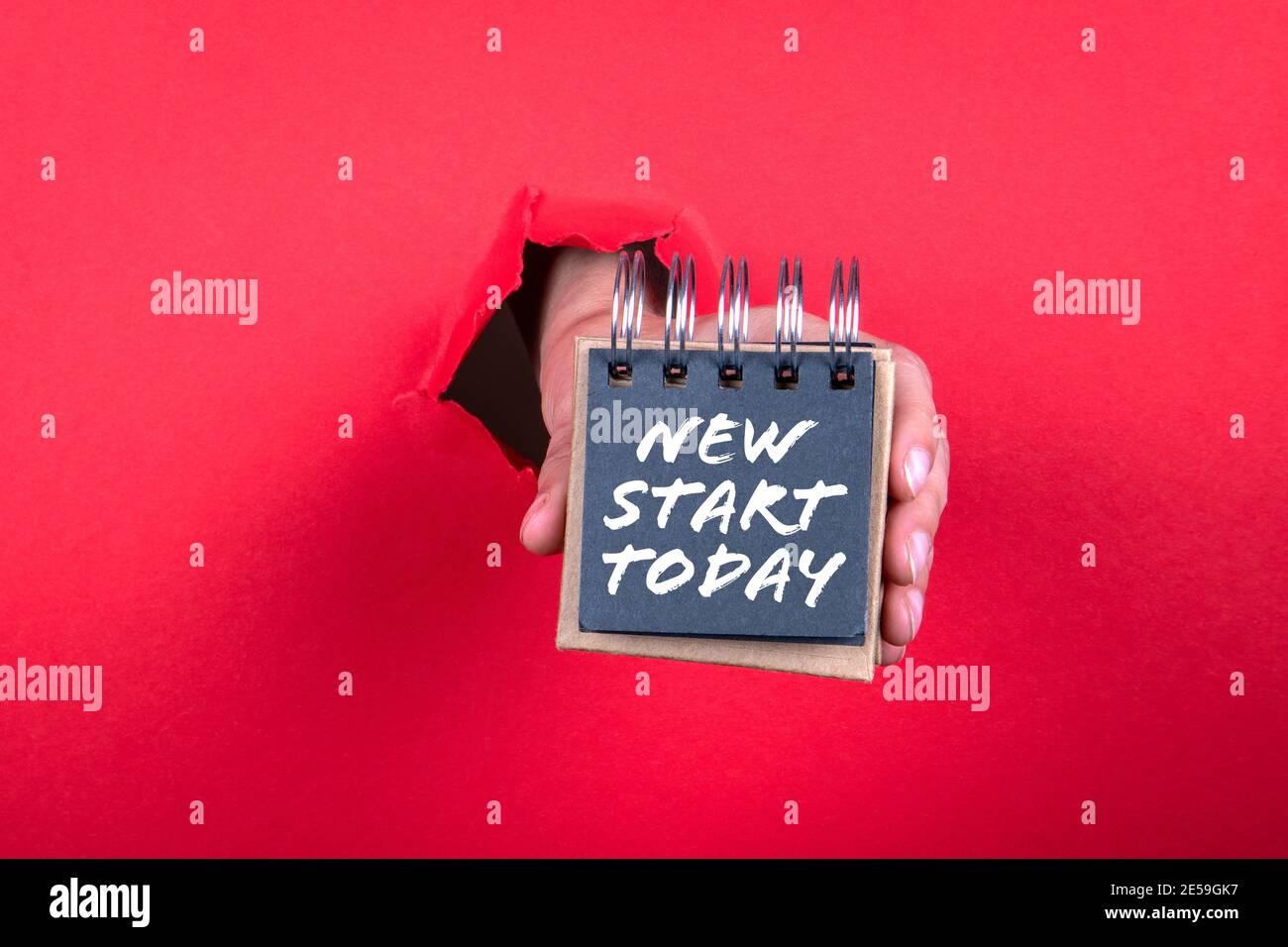Novità inizia oggi stesso. Taccuino in mano di un uomo su sfondo rosso. Foto Stock